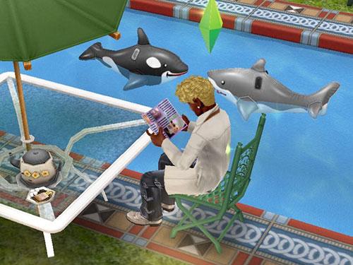 プールサイドで雑誌を読みふける男性シム。それを、おかしげに眺める、イルカとオルカの浮き輪たち(The Sims フリープレイ)