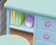青のベビーチェストの棚に本と並ぶペンギン(The Sims フリープレイ)
