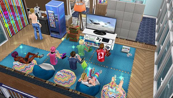 ビーチデリースの床、ブレイクダンス用マット、ビーンバックチェア、ゲーム機、デラックスなゲーム機、ピザの箱、ネオトーキョー冷蔵庫、高級ケトル、スレートのランドリーラック、白の北欧風ドア、パーティーリボンのドアなどをレイアウトした、ごろごろ休憩室(The Sims フリープレイ)